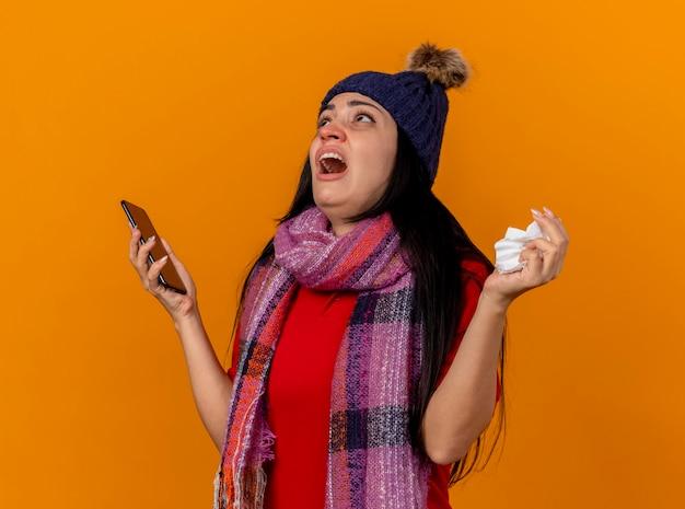 Giovane ragazza malata caucasica dispiaciuta che indossa cappello invernale e sciarpa tenendo il telefono cellulare e il tovagliolo che osserva in su isolato sulla parete arancione