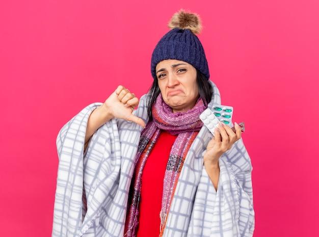 Giovane ragazza malata caucasica dispiaciuta che indossa cappello invernale e sciarpa avvolti in confezioni di plaid che tengono le pillole mediche che mostrano il pollice verso il basso isolato sul muro cremisi