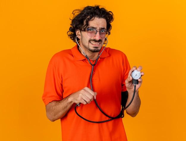 Giovane uomo malato caucasico dispiaciuto con gli occhiali e lo stetoscopio che tiene lo sfigmomanometro isolato sulla parete arancione con lo spazio della copia