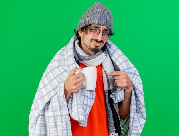 緑の壁に隔離されたカップを保持し、指している格子縞に包まれた眼鏡の冬の帽子とスカーフを身に着けている不機嫌な若い白人の病気の男
