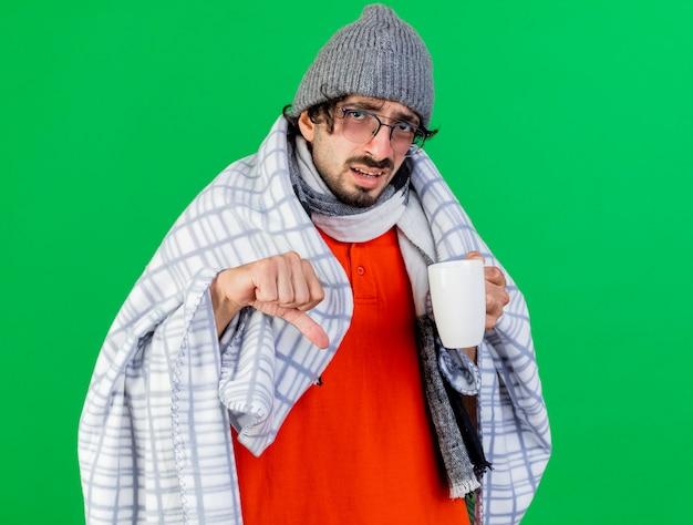 不機嫌そうな若い白人の病気の人は、コピースペースで緑の背景に分離された親指を下に向けてカメラを見て格子縞の保持カップに包まれた眼鏡の冬の帽子とスカーフを身に着けています