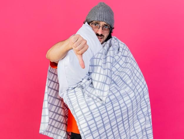 不機嫌そうな若い白人の病気の人は、コピースペースで真っ赤な背景に分離された親指を下に向けてカメラを見て格子縞の保持枕に包まれた眼鏡の冬の帽子とスカーフを身に着けています