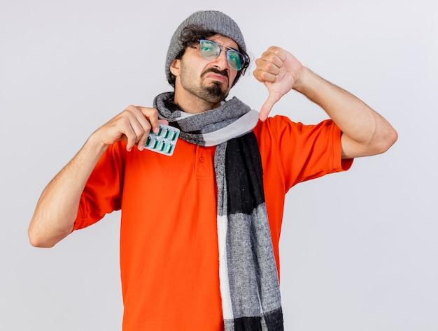 Giovane uomo malato caucasico dispiaciuto che indossa occhiali inverno cappello e sciarpa che tiene il pacchetto di capsule mediche che mostra il pollice verso il basso isolato sul muro bianco