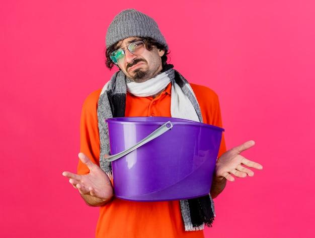 Giovane uomo malato caucasico dispiaciuto che indossa occhiali inverno cappello e sciarpa che tiene secchio di plastica che guarda l'obbiettivo che mostra le mani vuote isolate su fondo cremisi