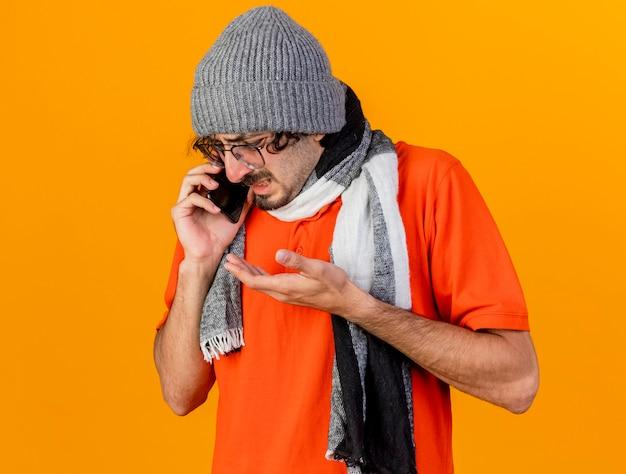 Giovane uomo malato caucasico dispiaciuto che indossa occhiali inverno cappello e sciarpa parlando al telefono che mostra la mano vuota guardando in basso isolato sulla parete arancione con lo spazio della copia