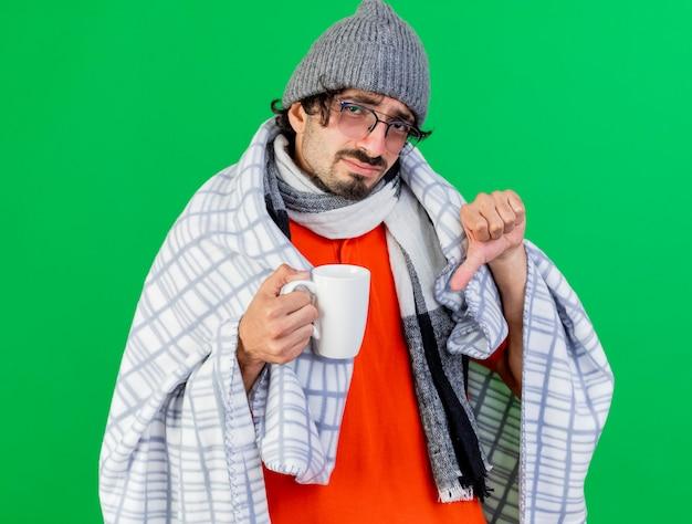 Giovane uomo malato caucasico dispiaciuto che indossa occhiali cappello invernale e sciarpa avvolti in una tazza di detenzione plaid che mostra il pollice verso il basso isolato sulla parete verde