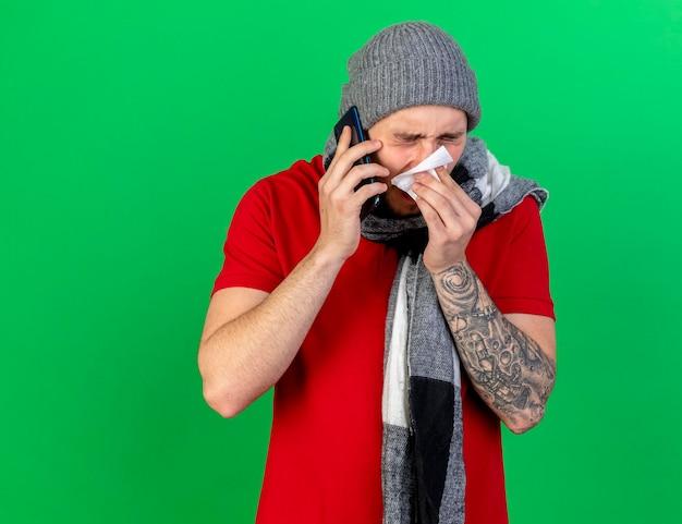 겨울 모자와 스카프를 착용하고 불쾌한 젊은 백인 아픈 남자가 녹색에 전화로 이야기하는 조직으로 코를 닦습니다.