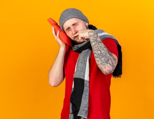 Il giovane uomo malato caucasico dispiaciuto che indossa il cappello e la sciarpa di inverno pulisce il naso con le dita e mette la testa sulla bottiglia dell'acqua calda isolata sulla parete arancione con lo spazio della copia