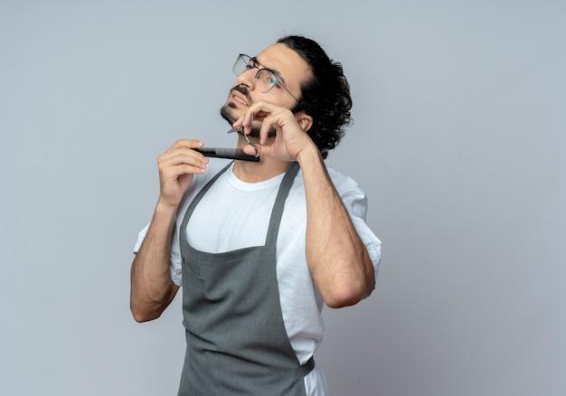 Недовольный молодой кавказский парикмахер в очках и с волнистой лентой для волос в униформе, стригущий и расчесывающий бороду, глядя прямо на белом фоне с копией пространства