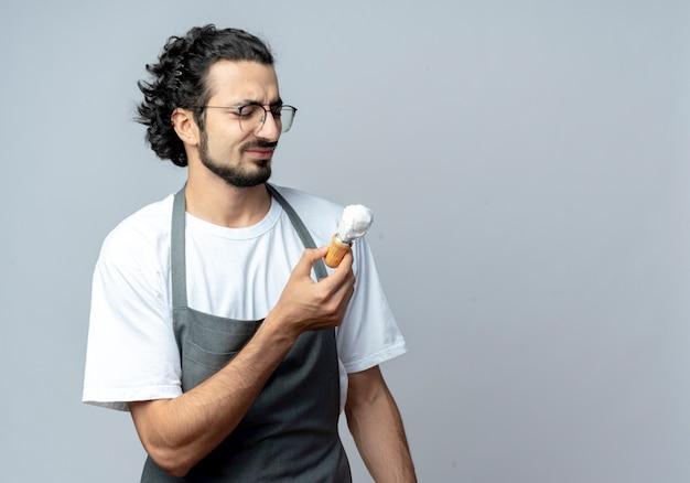 Недовольный молодой кавказский мужчина-парикмахер в очках и волнистой повязке для волос в униформе держит и смотрит на щетку для бритья, изолированную на белом фоне с копией пространства