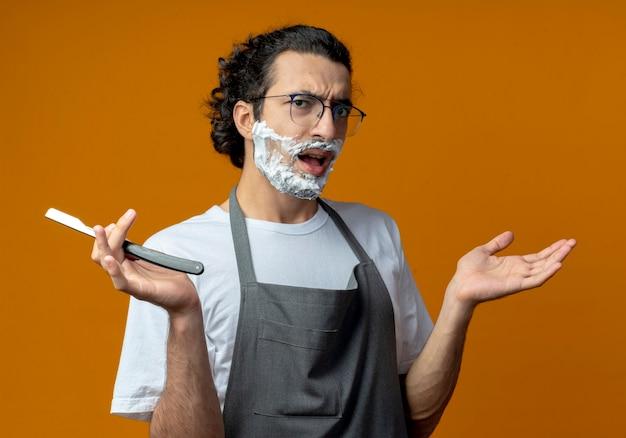 オレンジ色の背景で隔離された空の手を示す彼の顔に剃毛クリームを置いたストレートかみそりを保持している制服を着た眼鏡と波状のヘアバンドを身に着けている不機嫌な若い白人男性理髪師