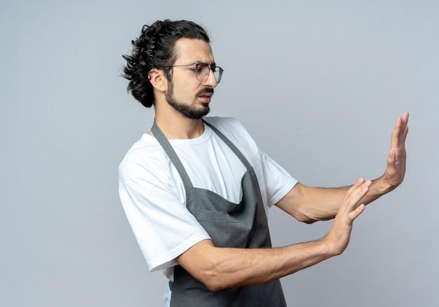Недовольный молодой кавказский парикмахер в очках и с волнистой лентой для волос в униформе смотрит в сторону и жестикулирует на белом фоне с копией пространства