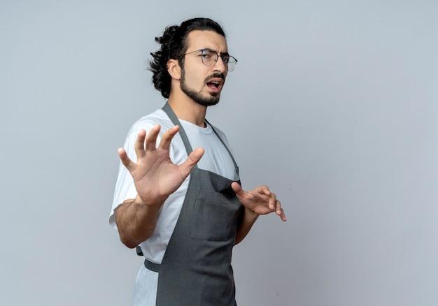 Недовольный молодой кавказский парикмахер в очках и с волнистой лентой для волос в униформе, стоящий в профиле, протягивая руку в камеру, жестикулируя не изолированно на белом фоне