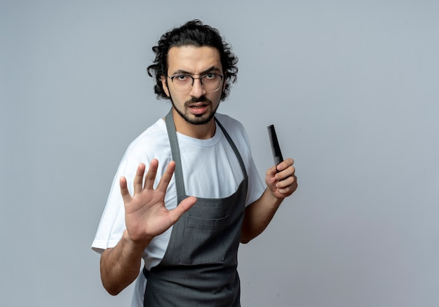 Unpleased young caucasian male barber wearing glasses and wavy hair band in uniform holding comb and stretching out hand at camera gesturing stop isolated on white background with copy space