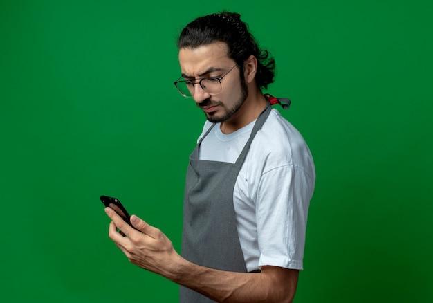 불쾌한 젊은 백인 남성 이발사 유니폼과 안경을 들고 프로필보기에 서서 복사 공간이 녹색 배경에 고립 된 휴대 전화를보고 입고