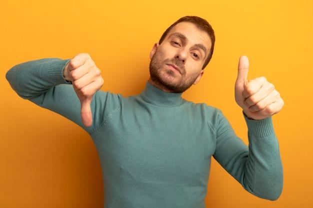 주황색 배경에 고립 된 엄지 손가락을 위아래로 보여주는 카메라를보고 불쾌한 젊은 백인 남자
