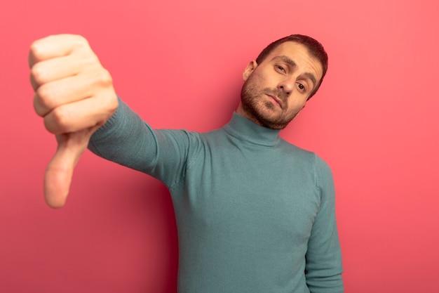 真っ赤な壁に孤立した親指を下に見せて不機嫌な若い白人男性