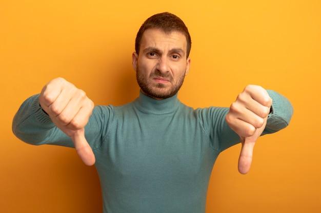 아래로 엄지 손가락을 보여주는 불쾌한 젊은 백인 남자는 오렌지 벽에 고립