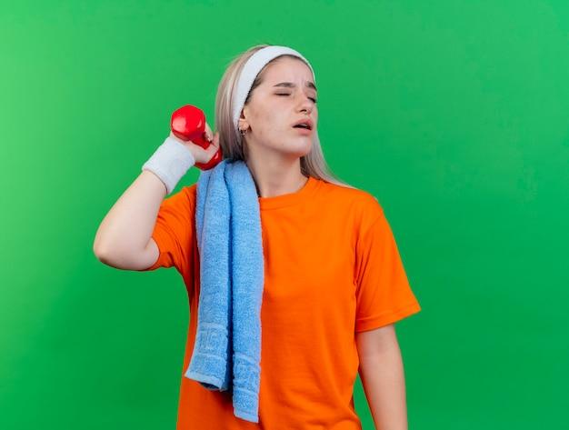 Недовольная молодая кавказская спортивная девушка с подтяжками, носящая повязку на голову и браслеты с полотенцем на плече, держит гантель