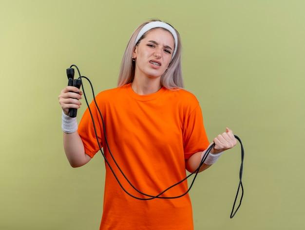 Una giovane ragazza sportiva caucasica scontenta con bretelle che indossa fascia e braccialetti tiene la corda per saltare