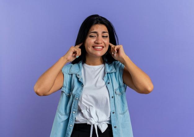 La giovane donna caucasica dispiaciuta chiude le orecchie che esaminano lato isolato su fondo viola con lo spazio della copia