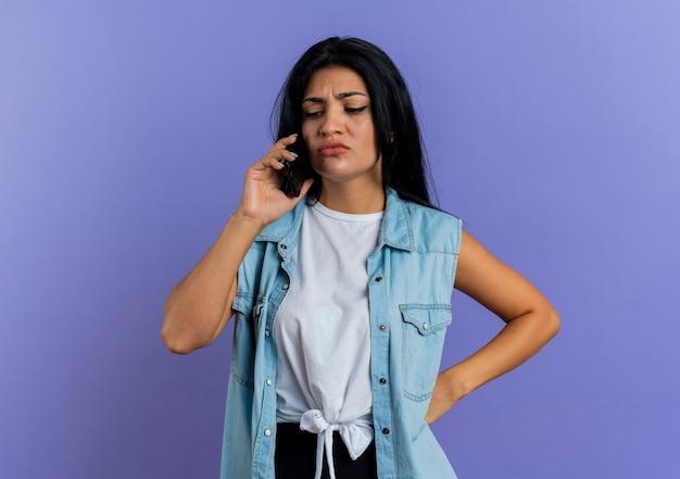 Soddisfatta giovane donna caucasica parla al telefono e mette la mano sulla vita isolata su sfondo viola con spazio di copia