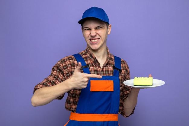 Giovane addetto alle pulizie scontento che indossa l'uniforme e tiene il cappuccio e indica la spugna sul piatto