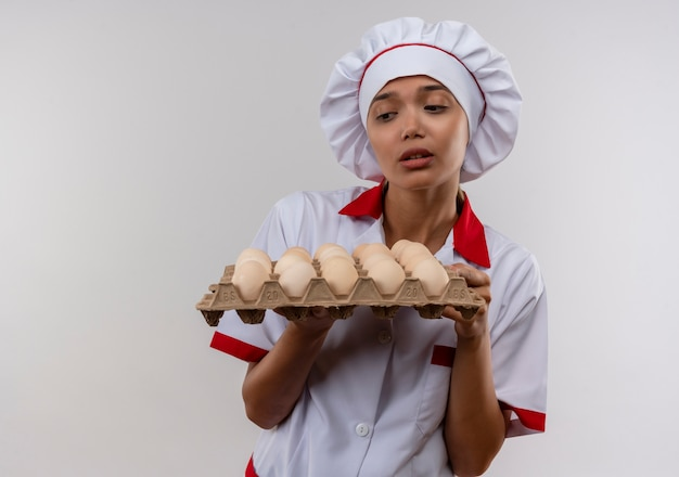 コピースペースで卵のバッチを見てシェフの制服を着た不機嫌な若い料理人の女性