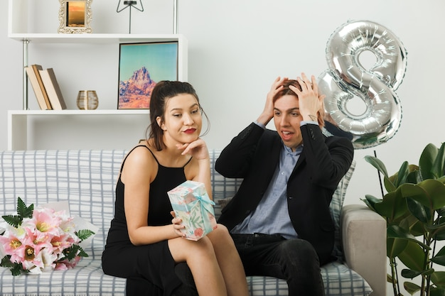 Unpleased young couple on happy women day holding present guy putting hands on head sitting on sofa in living room