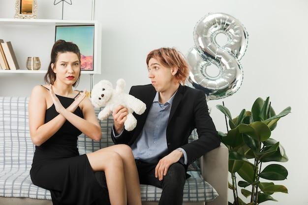 リビングルームのソファに座っていないジェスチャーを示すテディベアの女の子と幸せな女性の日に不機嫌な若いカップル