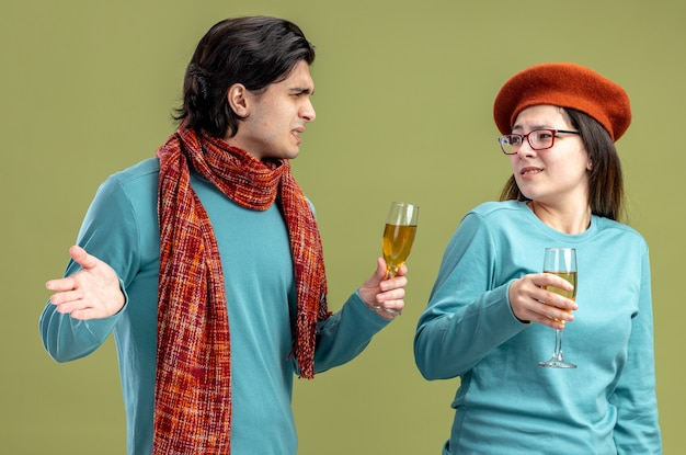 Unpleased young couple on valentines day guy wearing scarf girl wearing hat holding glass of champagne looking at each other isolated on olive green background