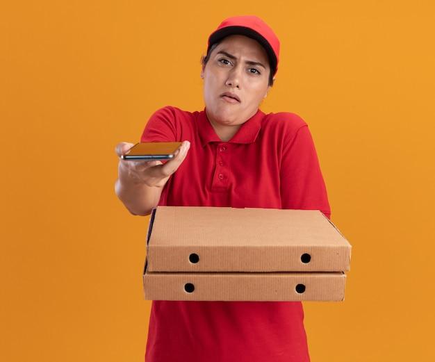 Недовольная молодая доставщица в униформе и кепке держит коробки с пиццей и протягивает телефон впереди, изолированную на оранжевой стене