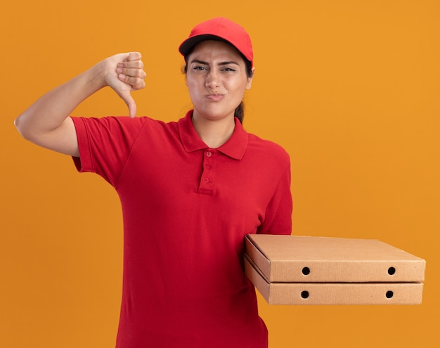 Una giovane ragazza delle consegne scontenta che indossa l'uniforme e il berretto che tiene le scatole della pizza che mostra il pollice giù isolato sulla parete arancione