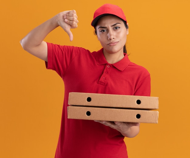 Unpleased young delivery girl wearing uniform and cap holding pizza boxes showing thumb down isolated on orange wall