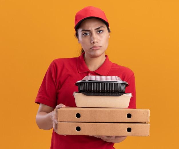 Una giovane ragazza delle consegne scontenta che indossa l'uniforme e il berretto che tiene in mano scatole per pizza con contenitori per alimenti isolati su una parete arancione