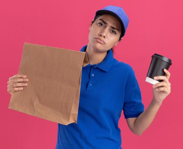 Недовольная молодая доставщица в униформе с кепкой держит бумажный пакет продуктов с чашкой кофе, изолированным на розовой стене