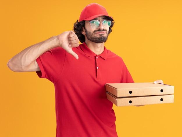 Недовольный молодой курьер в красной форме и кепке в очках, держащий упаковки с пиццей, глядя вперед, показывая большой палец вниз, изолированный на оранжевой стене