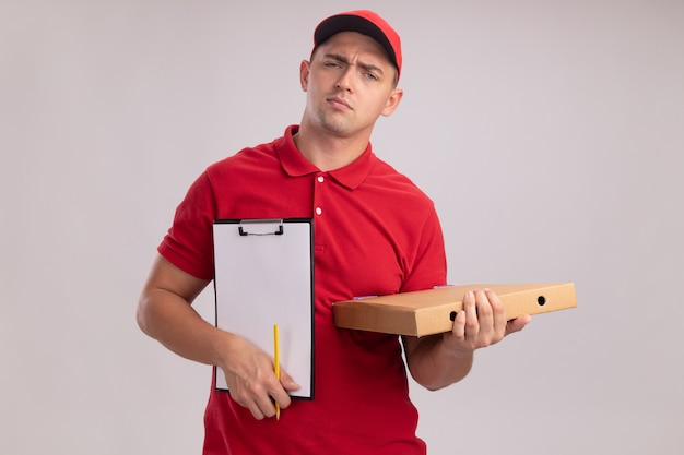흰 벽에 고립 된 피자 상자 클립 보드를 들고 모자와 유니폼을 입고 불쾌한 젊은 배달 남자