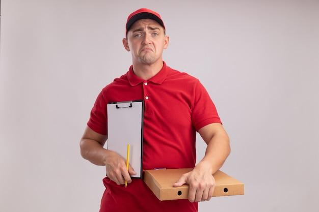 Giovane uomo di consegna dispiaciuto che indossa l'uniforme con il cappuccio che tiene appunti con la scatola della pizza isolata sulla parete bianca