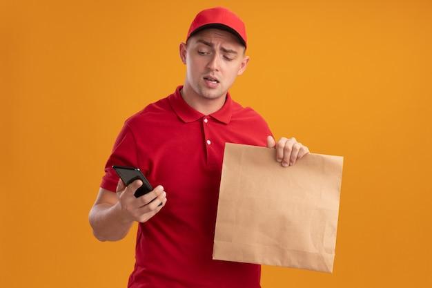 Giovane uomo di consegna dispiaciuto che indossa l'uniforme con cappuccio che tiene il pacchetto di cibo di carta guardando il telefono in mano isolato sulla parete arancione