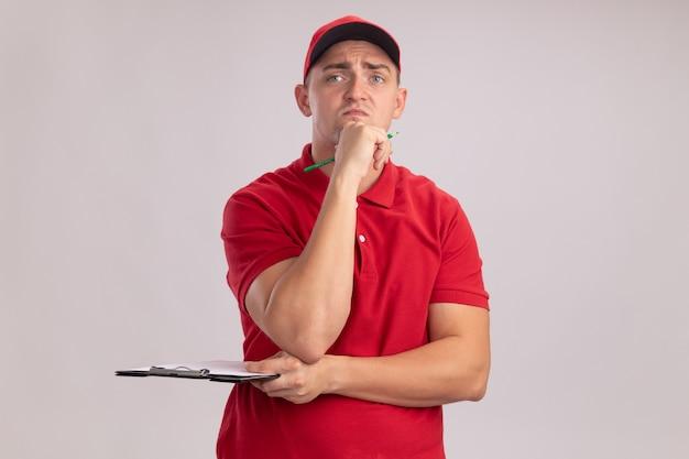 クリップボードと鉛筆を保持し、白い壁で隔離のあごに手を置くキャップで制服を着て不機嫌な若い配達人