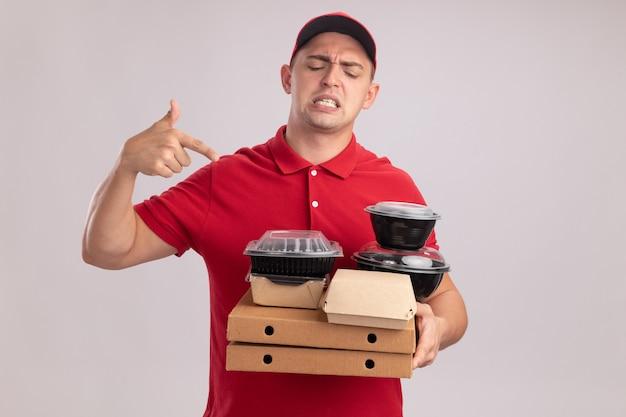 Giovane uomo di consegna scontento che indossa l'uniforme con la tenuta del cappuccio e indica i contenitori per alimenti su scatole per pizza isolate sul muro bianco