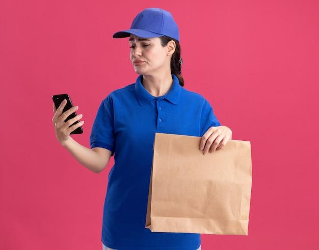 분홍색 벽에 격리된 전화기를 보고 있는 종이 패키지와 휴대폰을 들고 있는 유니폼과 모자를 쓴 불쾌한 젊은 배달 여성