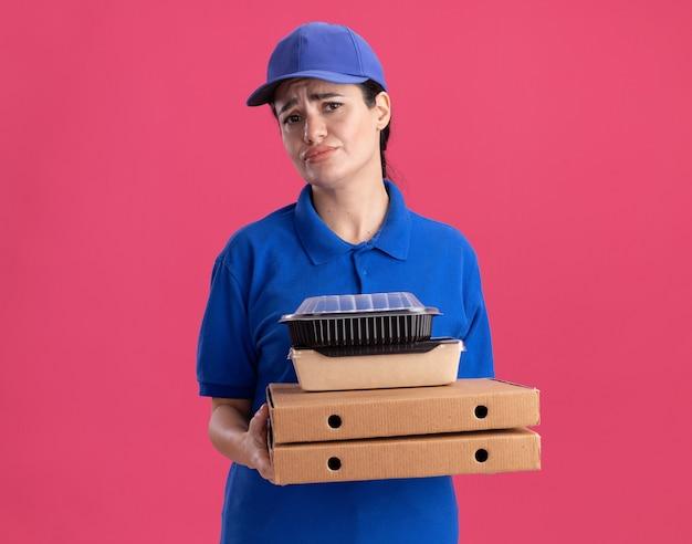 Giovane donna delle consegne scontenta in uniforme e cappello che tiene in mano confezioni di pizza con una confezione di carta per alimenti e un contenitore per alimenti su di esse