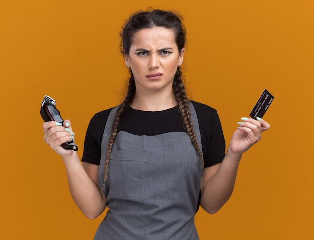 Unpleased young female barber in uniform holding credit card and hair clippers isolated on orange wall