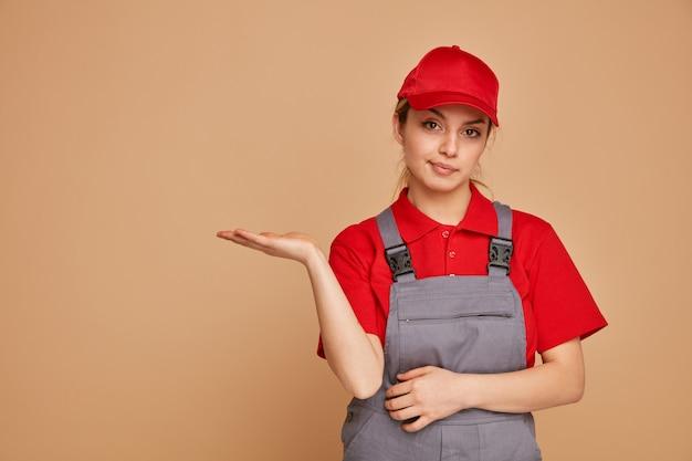 유니폼과 모자를 쓰고 빈 손을 보여주는 불쾌한 젊은 여성 건설 노동자