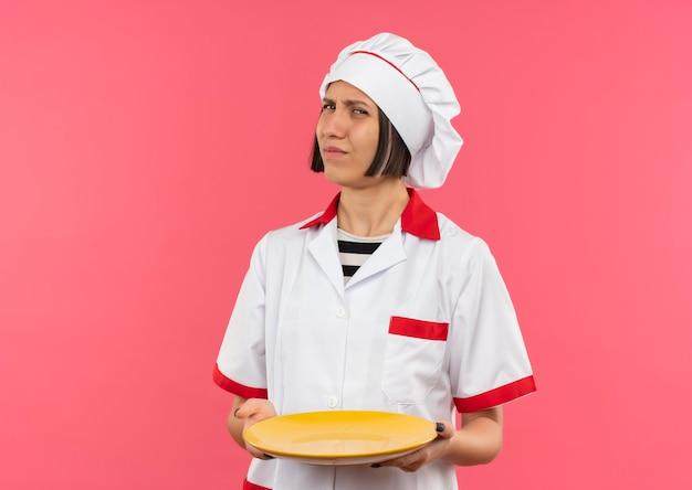 Giovane cuoco femminile insoddisfatto in uniforme del cuoco unico che tiene piatto vuoto isolato su fondo rosa con lo spazio della copia