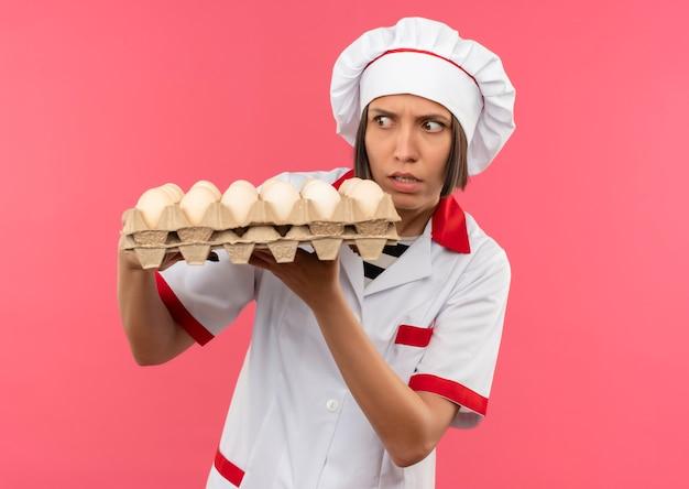 Giovane cuoco femminile dispiaciuto in uniforme del cuoco unico che tiene e che esamina il cartone delle uova isolato su fondo rosa