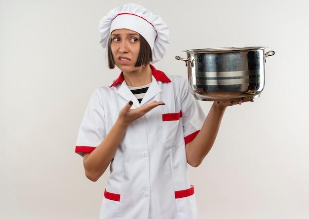 Giovane cuoco femminile dispiaciuto nella tenuta dell'uniforme del cuoco unico e che indica con la mano alla pentola che esamina il lato isolato su fondo bianco con lo spazio della copia