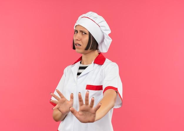 コピースペースでピンクの背景に分離されたカメラで身振りで示すシェフの制服を着た不機嫌な若い女性料理人
